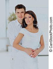 man hugs a woman looking at the camera.