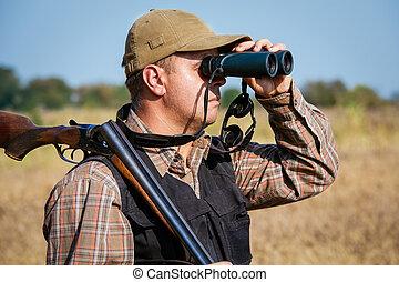 Man hunter with shotgun looking through binoculars