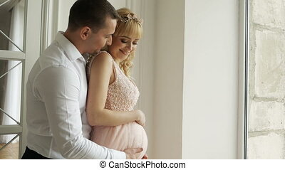man husband embracing belly of his pregnant wife in dress