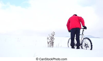 Man iker is pushing bike in deep snow at dry bush of thistle . Cloudy winter day with gentle wind and small snow flakes in the air.
