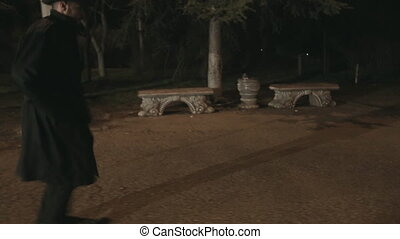 Man in a black cloak and hat runs through the park at night for someone