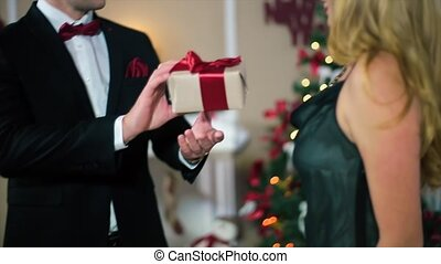 Man in a Black Suit Gives a Woman in Evening black dress a gift with a red ribbon the woman a broad smile in a white room with fireplace and Christmas tree