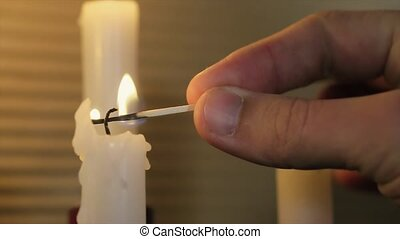 Man in a Black Suit Matches Three Lights Candles