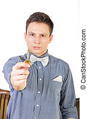 Man in a blue shirt with a bow tie holds the key