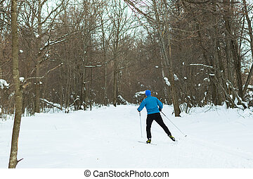 Man in a blue suit runs on skis in the winter woods. Ice...