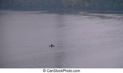 Man in a boat floats on a river on an overcast and cold...