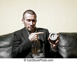 Man in a business suit showing on the clock