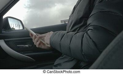 Man in a car login in on a smart phone with the fingerprint reader