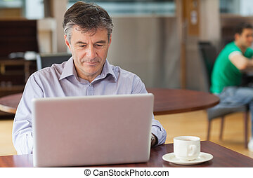 Man in a coffee shop working on the laptop - Man sitting in...