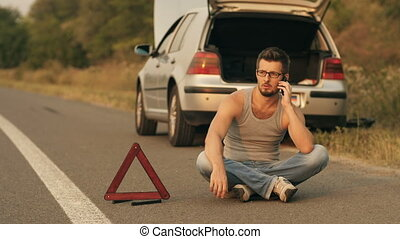 Man in a front of broken car with cell phone - Road trip car...