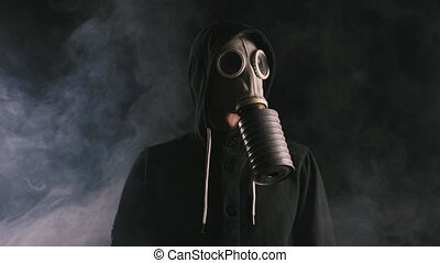 man in a gas mask in smoke in a dark room - Smoke rising...