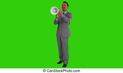 Man in  a gray suit shouting through a megaphone