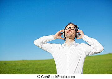 Man in a green field enjoying his music