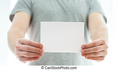 Man in a grey t-shirt holding a blank card