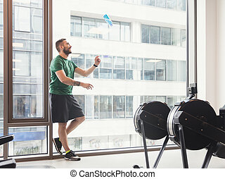Man in a gym throwing a bottle up in the air.