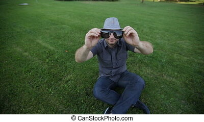 man in a hat dresses sunglasses on a summer meadow.