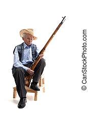 Man in a hat sitting with a gun