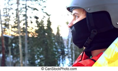 man in a helmet riding a mountain on a lift with a snowboard on a background of trees, mountains and sun