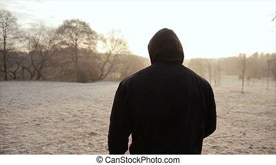 man in a hood walking in the park. slow motion