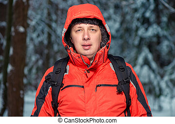man in a jacket on a hike with a backpack in the winter forest