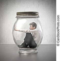 man in a jar - young businessman closed in a jar on gray ...