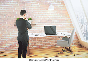 Man in a loft room with desk and chair