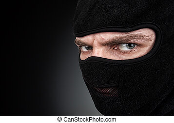 Man in a mask on black background