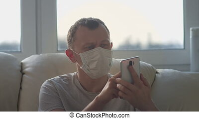 Man in a medical mask uses his mobile phone, sits at home on the couch.