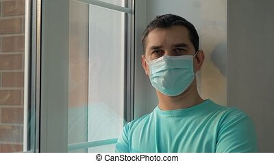 Man in a medical mask while at home isolation