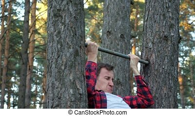 man in a plaid shirt hardly pulls himself on a horizontal bar in the forest, slow motion