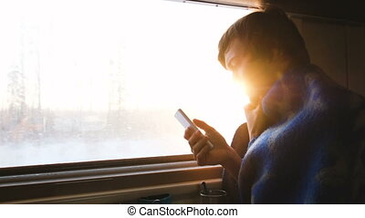Man in a plaid traveling in a train and using the smartphone...