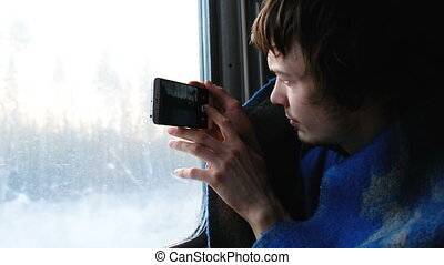 man in a rug travels by train and takes pictures of nature on the phone, the camera shows the view from the window, nature through the train window, 4k.