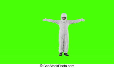 Man in a spacesuit stands and shows with both hands in opposite directions
