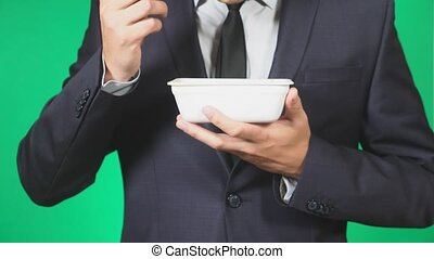 Man in a suit eats Chinese noodles, close-up, 4k, green background, slow-motion, copy space.