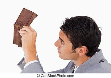 Man in a suit looking in his empty wallet