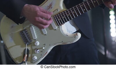 Man in a suit plays six-string electric guitar at concert. Close-up footage of musiian's hands at party with strobe disco lights.