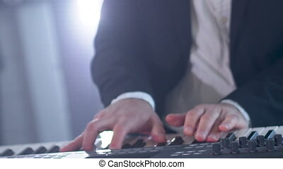 Man in a suit plays six-string electric synthesizer at concert. Close-up footage of musiian's hands at party with strobe disco lights.