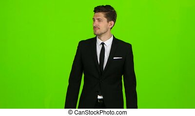 Man in a suit walks along the street, looks around. Green Screen