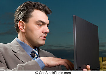 man in a suit with laptop