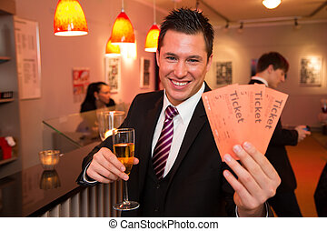 Man in a theatre or cinema presenting tickets - Handsome man...
