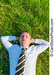man in a tie sleeping on the lawn