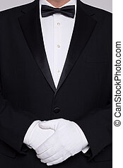 Man in a tuxedo wearing white gloves. - Torso of a man...