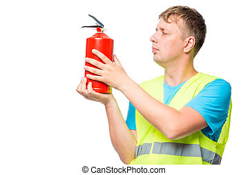 Man in a vest holds a fire extinguisher in the hands on a white background