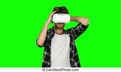 Man in a virtual reality mask looks around. Green screen. Close up