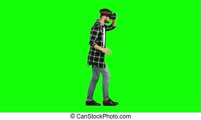 Man in a virtual reality mask walking. Green screen