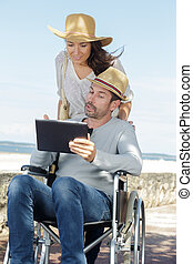 man in a wheelchair and woman are walking outdoors