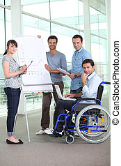 Man in a wheelchair at work in the office with his colleagues