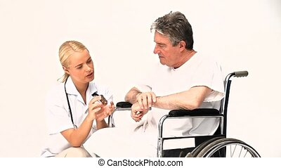 Man in a wheelchair listening his nurse against a white...