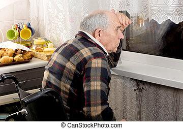 Man in a wheelchair peering through a window