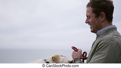 Side view of a Caucasian man in a wheelchair enjoying taking a walk with his dog in the countryside by the sea, playing with his dog in slow motion